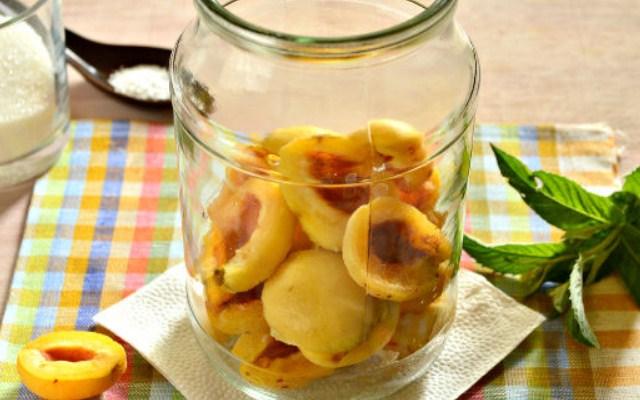 разложить половинки абрикосов по банкам