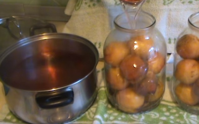 заливаем персики горячим компотом