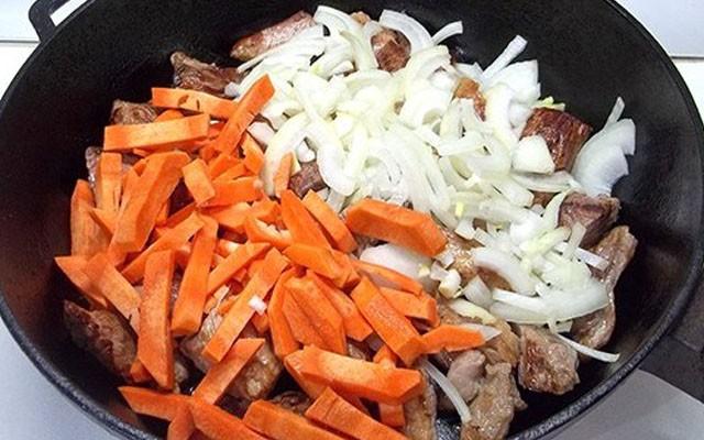обжарить мясо, затем добавить к нему лук и морковь