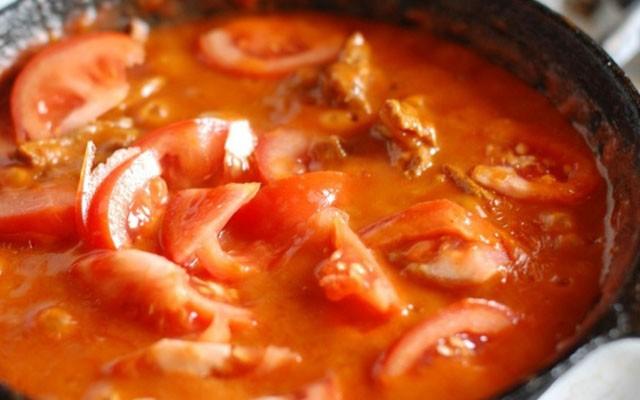 соединить лук с мясом, влить бульон, добавить огурцы, чеснок и томаты
